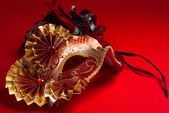 A red and gold feathered Venetian mask on red background — Stock Photo