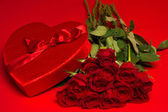 Roses and a red heart box on a red background — Stock Photo
