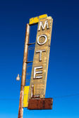 Vintage, neon, decrepit motel sign with a sky background — Stock Photo