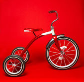 Vintage red tricycle on a bright red background — Stock Photo