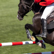 Rider on a high jump competition - Stock Photo