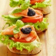 Three sandwiches with salmon and caviar — Stock Photo
