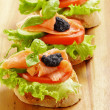 Three sandwiches with salmon and caviar — Stock Photo #12553737