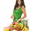 Woman with variety of fruits in wicker basket isolated on white — Stock Photo