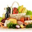 Composition with groceries in wicker basket on kitchen table — Stock Photo