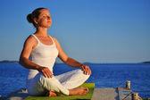 Jovem mulher durante yoga meditação na praia — Foto Stock