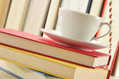 Composition with stack of books and cup of coffee — Stock Photo