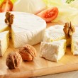 Composition with different sorts of cheese on wooden table - Stock Photo