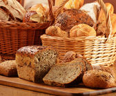 Composition with bread and rolls in wicker basket — Stockfoto
