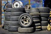 Stacks of old used tires in front of the auto service station — Stock Photo