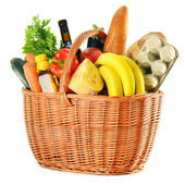 Wicker basket with variety of grocery products isolated on white — Stock Photo