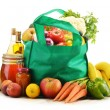 Green shopping bag with grocery products on white background — Stock Photo