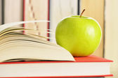 Composition with green apple and books on the table — Stock Photo