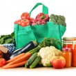 Green shopping bag with assorted grocery products isolated — Photo