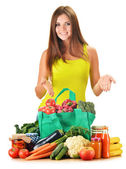 Young woman with variety of grocery products in shopping bag — Stock Photo