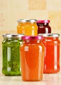 банки фруктовыми джемами на кухонном столе. консервированные фрукты — Стоковое фото