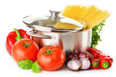 Stainless pot with spaghetti and variety of raw vegetables — Stock Photo