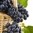 Wicker basket full of fresh red grapes isolated on white — Stock Photo