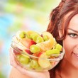 Young woman holding glass bowl with fruit salad — Stock Photo #35112039
