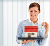 Young woman holding small house and keys — Stock Photo