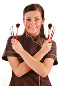 Professional beautician holding brushes — Stock Photo