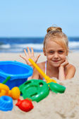Little girl playing on the sand beach — Stock Photo