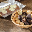 Stock Photo: Chocolates and chocolate in basket on wooden table