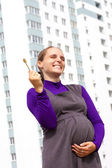 Smiling pregnant woman with key from new apartment — Stock Photo