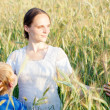 Mother with her child in a field — Stock Photo #12346022