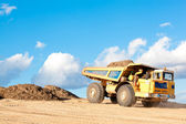 Heavy dump truck unloads soil on the sand — Stock Photo