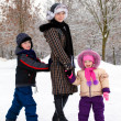 Stock Photo: Mother and children relaxing at snow