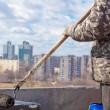Stock Photo: Roofer worker painting black coal tar or bitumen at concrete surface by roller brush