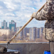 Roofer worker painting black coal tar or bitumen at concrete surface by the roller brush — Stock Photo