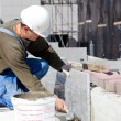 Stock Photo: Tiler installing marble tiles at construction site