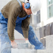 Stock Photo: Industrial worker makes horizontal cut