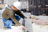Dlaždič instalace mramorové dlaždice na staveništi — Stock fotografie