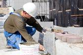 Ladrilhador instalando telhas de mármore no canteiro de obras — Foto Stock