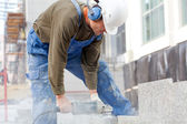 Industrial worker makes a horizontal cut — Stock Photo