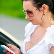Young woman reading message on mobile phone — Stock Photo