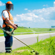 Stock Photo: Road landscaper cutting grass using string lawn trimmer