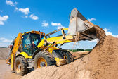 Excavator machine unloading sand with water — Stock Photo