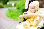 Smiling baby girl sitting in a stroller — Stock Photo