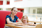 Mom and daughter relaxing in cafe — Stockfoto