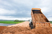 Dump truck unloading sand during road works — Stock Photo
