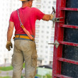 Stock Photo: Construction worker hammering pin for assembling concrete formwo