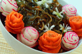 Sea cabbage decorated by a carrot and radish — Stock Photo