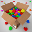 Cardboard box filled with coloured hearts — Stock Photo
