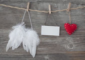 Angel wings with heart and blank note — Stock Photo