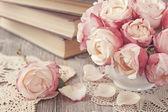 Rosa rosen und alte bücher — Stockfoto