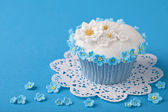 Cupcake with white and blue flowers — Stock Photo